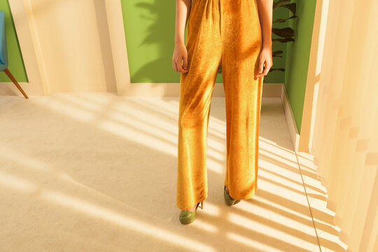 young woman wearing a yellow velvet jumpsuit