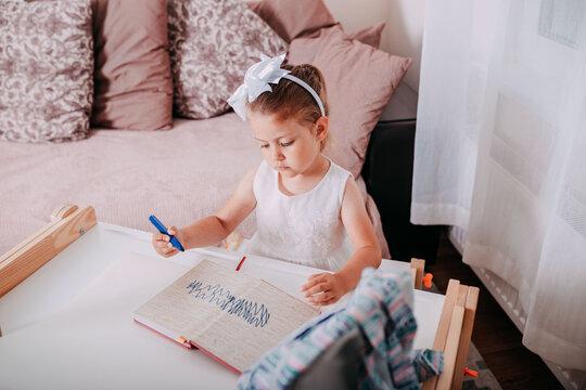Little girl in the school near the school desk. A girl writes in notebook. School supplies on the desk.