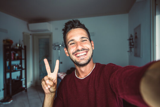 Happy young handsome millennial taking a selfie smiling at the camera in the living room at home.