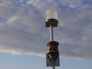 Navigation top lighting and anchor light attached to a metal rod attached to a yacht, the lamps covers is made of plastic. The entire construction is attacked by weather in connection with pollution
