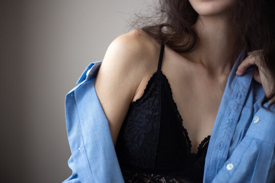 Portrait of young woman with brunette curly hair wearing blue oversize shirt and lacy bra over simple background.