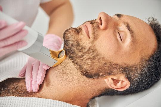 Handsome bearded man having laser hair removal procedure
