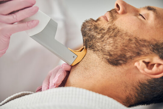 Good-looking young man undergoing laser hair removal procedure