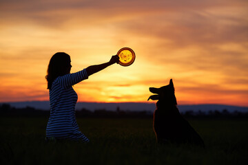 Black, side silhouette of a kneeling woman with an orange disc in her outstretched hand and an attentive, watching dog while training against a colorful, orange evening sky. Woman and dog.
