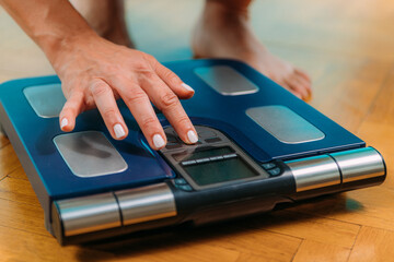 Woman Measuring Body Composition with Digital Scale Monitor
