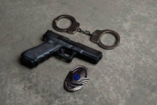 A gun, police badge and handcuffs laying on concrete surface