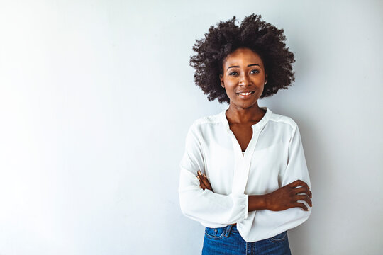 Close up attractive young black woman. Photo of young curly girl. Studio shot of a young businesswoman against a gray background. Portrait of young woman looking to camera with arms crossed