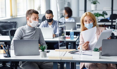 Social distancing and document management. Millennial guy and woman in protective masks discuss work issues through protective board
