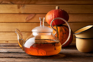 teapot with brewed hot tea ,pumpkin fnd cookies on a wooden, cozy background