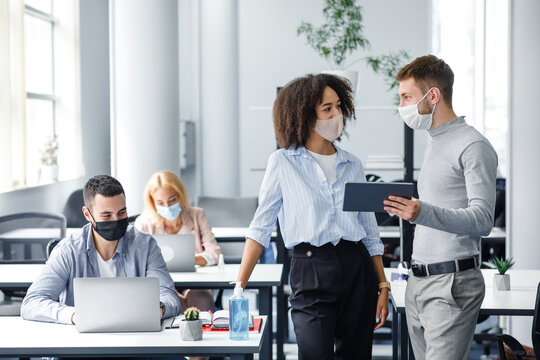 Discuss with colleague about project. Guy in protective mask shows tablet to african american lady and consults about work, in interior of modern office during outbreak