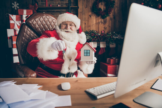 Jolly grey white hair beard santa claus x-mas real estate agent sit table show small bulding keys christmas season sale wear red cap headwear in house indoors with advent noel decoration