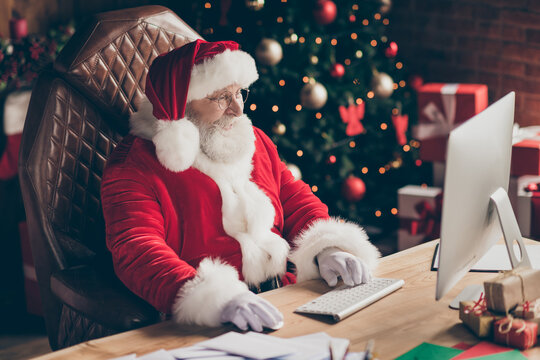 Profile side photo of santa claus sit table desk work computer before x-mas christmas night midnight check email read kids gift present wish list in house indoors wear cap headwear