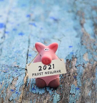 Kleines rosa Glücksschwein, mit Tafel und Aufschrift: 2021 Prost Neujahr, auf altem, blauen Holz.
