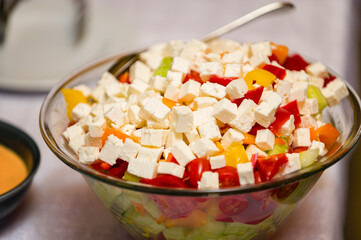 Cheese and tomato cubes in a glass bowl at a celebration.