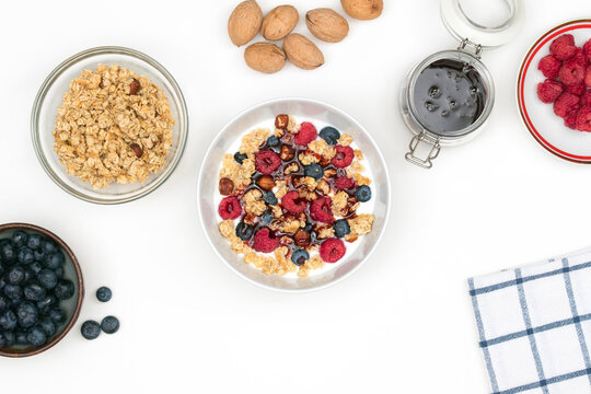 Natural yogurt with granola, fresh raspberries, blueberries and nuts with date syrup in a ceramic bowl on a white table. Top view on healthy breakfast or dessert with ingredients.