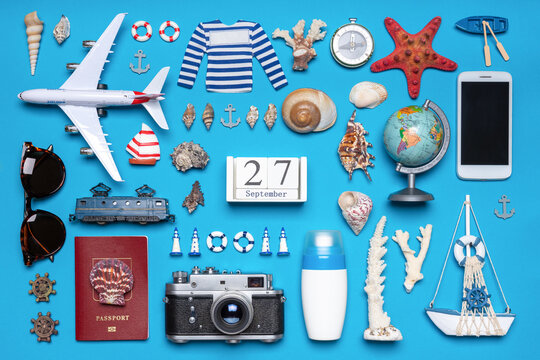 Happy world tourism day. Touristic objects, smart phone, passport, photo camera, sunglasses and decorative items on blue background. Flat lay, top view. Calendar date September 27, world tourism day