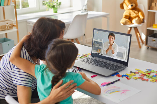 Mother and daughter communicating online with young woman doctor on laptop