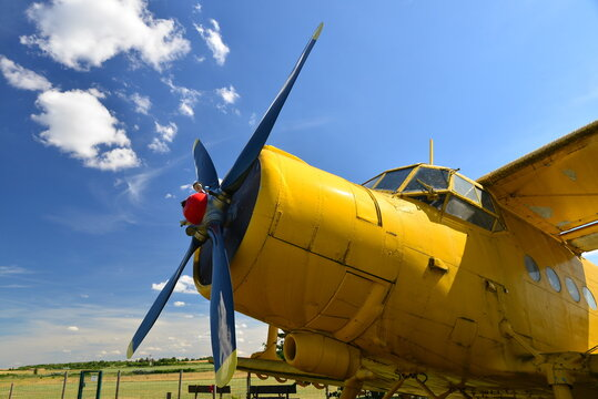 Close-up view of an old yellow plane. Isolated yellow bi plane on grassy meadow under blue sky with dynamic clouds. Aircraft at a grassy airfield.