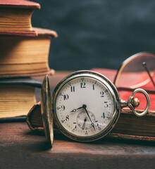 Pocket watch and old books on a wooden office desk background.
