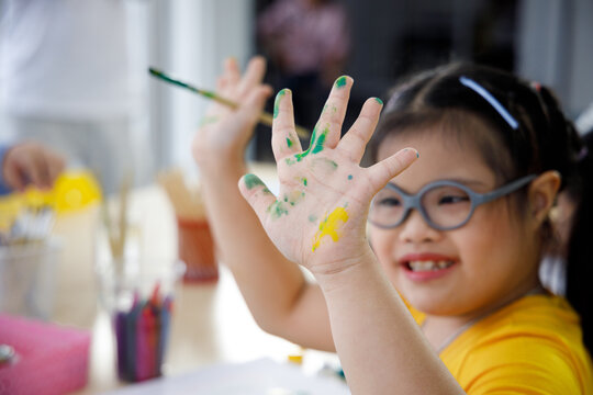Asian girl with Down's syndrome painting her hand.