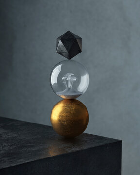 Stacked gold sphere, glass ball, and black polyhedron