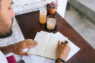 Crop anonymous man writing notes with pen in notebook while sitting at table in cafe