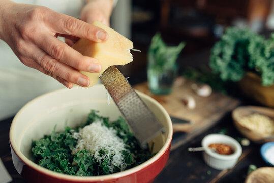 Woman grating parmesan cheese into kale salad