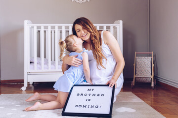 Pregnant mother and her daughter playing with a letter board written My Brother is Coming