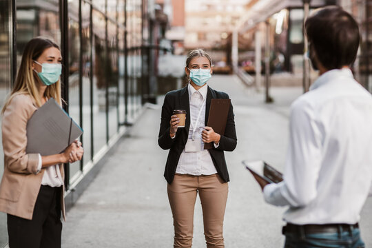 Three employers standing in social distance wearing face mask looking at each other and talking