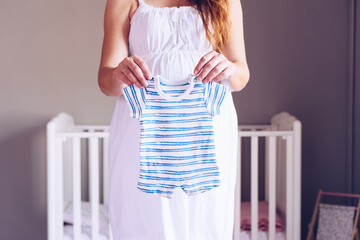 Pregnant woman shows baby clothes