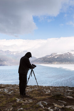 Man filming glaciers from the overlook in the summer in Patagonia