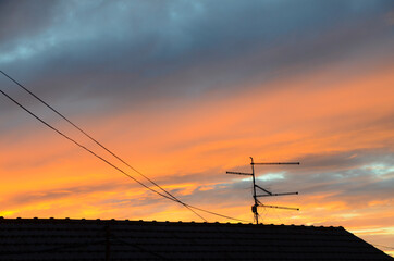 Television antenna on the roof of house at sunset. Orange sunset over the city. Silhouette of TV...