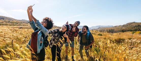 Fototapeta Friends taking selfie on hiking trip