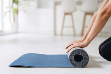 Close up of woman hands prepairing fitness mat for yoga or workout classes at home on a floor. Time for meditation, fitness sessions, virtual online yoga, wellbeing and wellness concepts