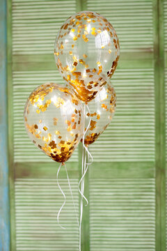 Ballons with gold confetti on green background