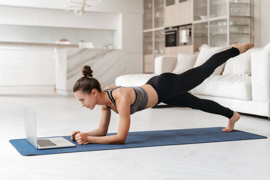 Athletic beautiful woman training at home in her apartment, doing plank exercise with online tutorial, watching virtual fitness workout class on laptop. Sport, wellness and health lifestyle concept