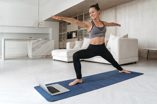 Sporty woman practicing yoga at home because of social distancing, using laptop for online class, standing in Warrior two exercise, Virabhadrasana II, working out. Yoga instructor performs exercise
