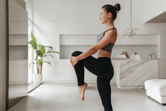 Young handsome sporty woman in sportswear doing stretching and balancing yoga exercise at home in living room. How to stay healthy on quarantine concept. Fitness, work out, healthy lifestyle concept