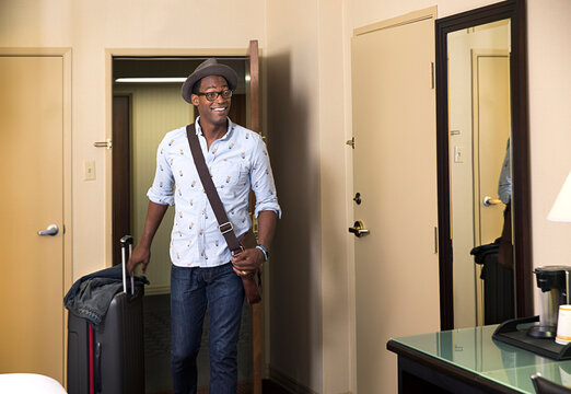 Black man with rolling suitcase entering hotel room