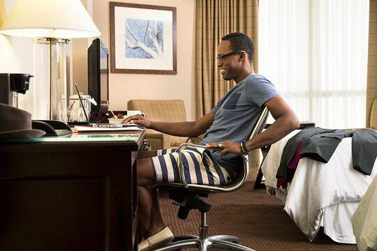 Smiling Black man in hotel room using laptop