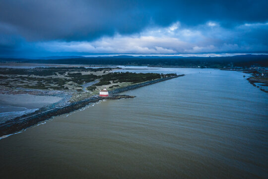 Aerial of lighthouse in Bandon, Oregon, USA with storm clouds.