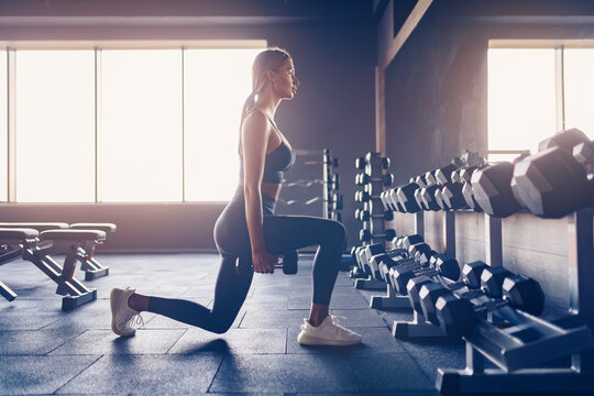 Beautiful girl doing lunges exercise with dumbbells in gym.