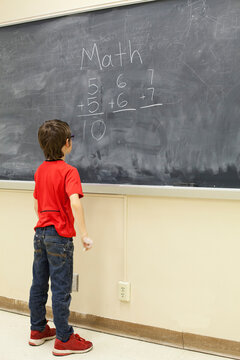 Boy solves math problems on the chalkboard in the front of the classroom