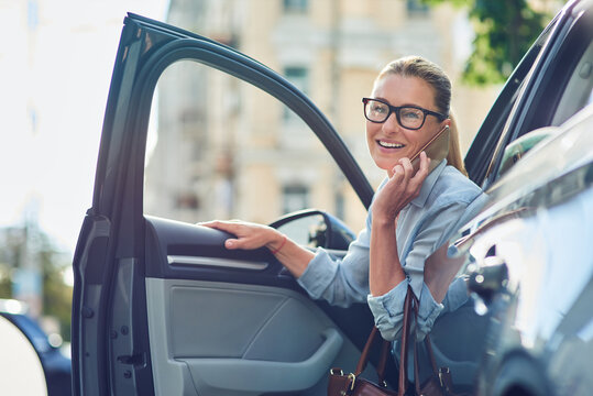 Attractive happy business woman in classic wear getting out of her modern car, talking on mobile phone and smiling, arrived at work