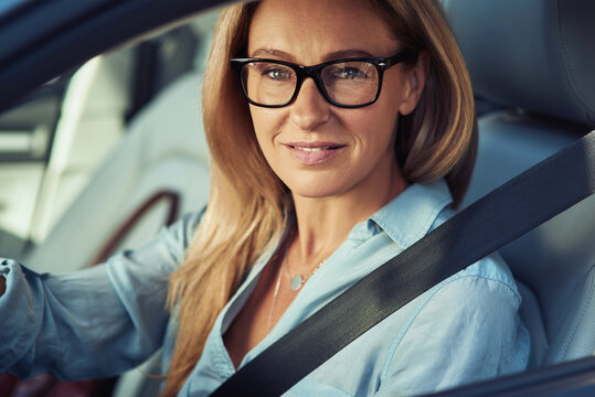 Portrait of a beautiful mature business woman driving a car, sitting behind steering wheel, looking at camera and smiling