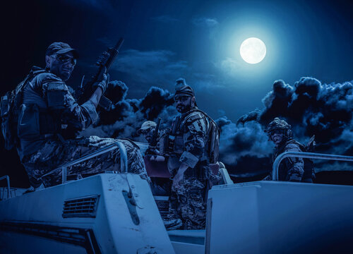 Commando fighters team, equipped and armed Navy SEALs soldiers on speed boat deck, preparing to secret mission or raid, patrolling coastline at night. Special forces shooters on boat at full moon
