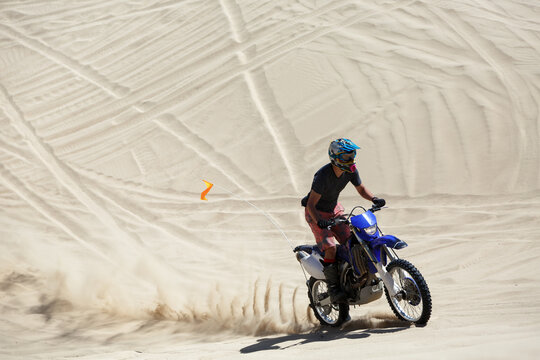 Teenager riding a motorcycle on a sand dune