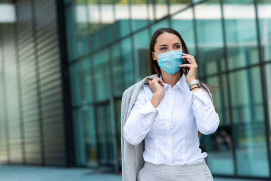 Business woman with mask talking on phone outdoor