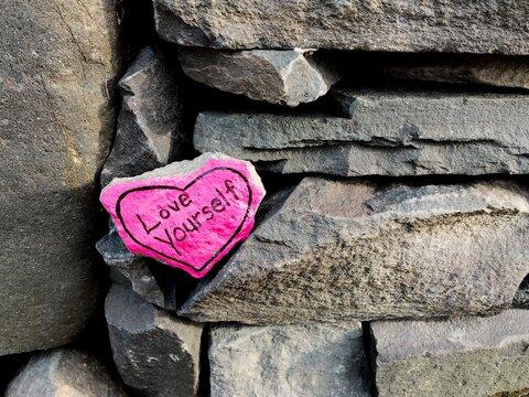 love yourself heart-shaped rock
