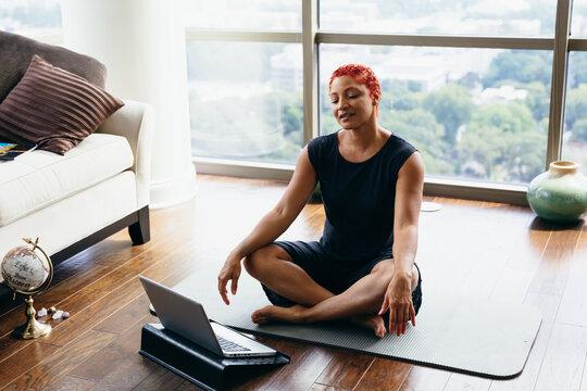 Woman doing virtual group meditation workout at home